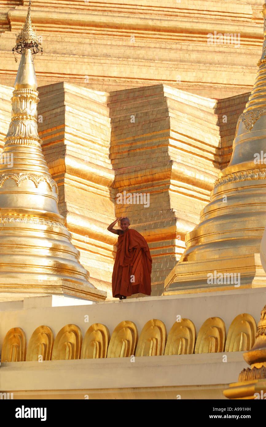 Red robed monk surrounded by golden spires of the dramatic Shwedagon Pagoda in Yangon(Rangoon) Myanmar (Burma) - Stock Image