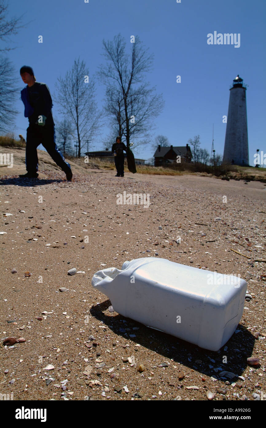A person walks past trash on a beach during a cleanup in New Haven Connecticut USA - Stock Image