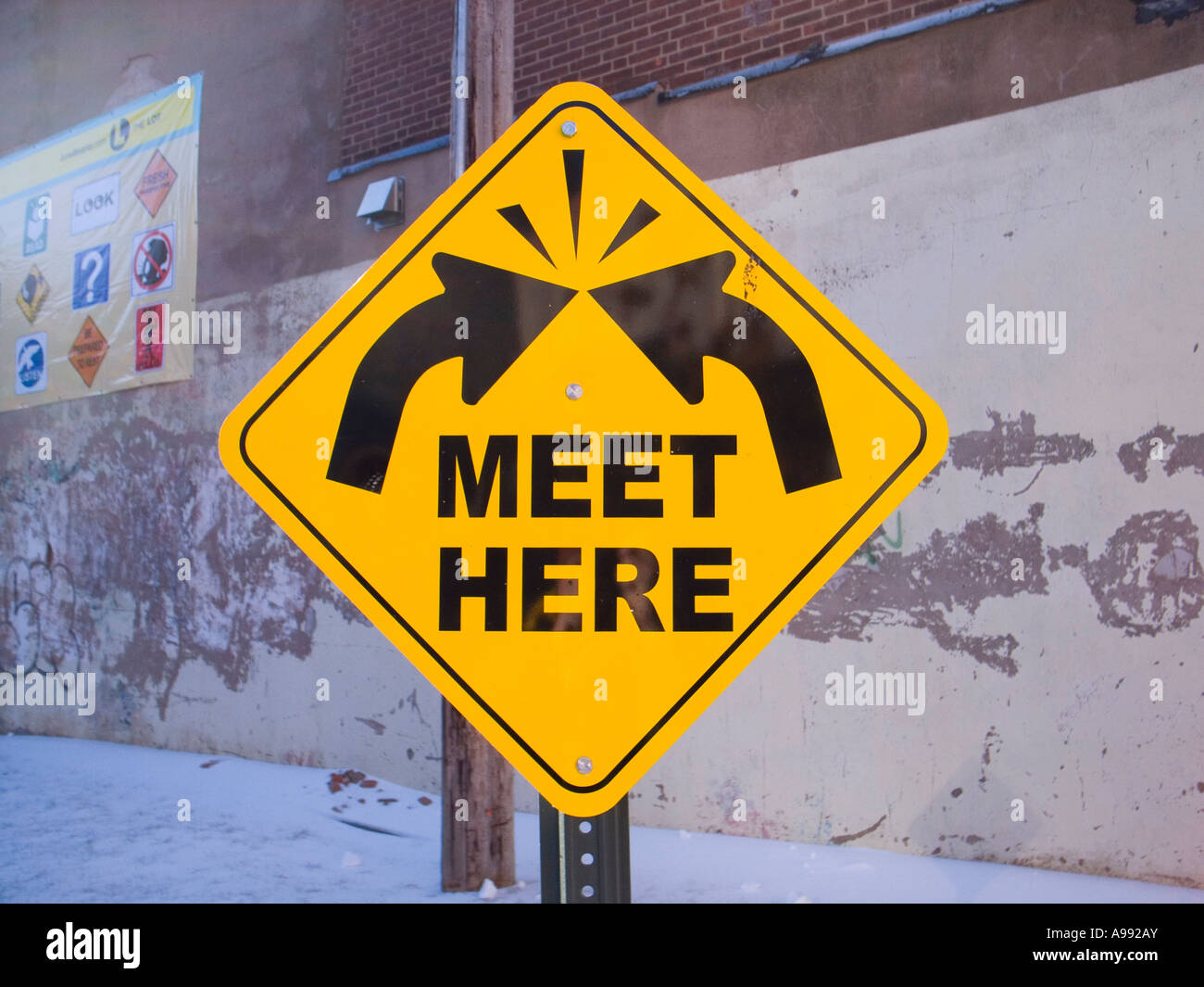 Conceptual sign with arrows asks viewer to meet here outdoor artwork - Stock Image