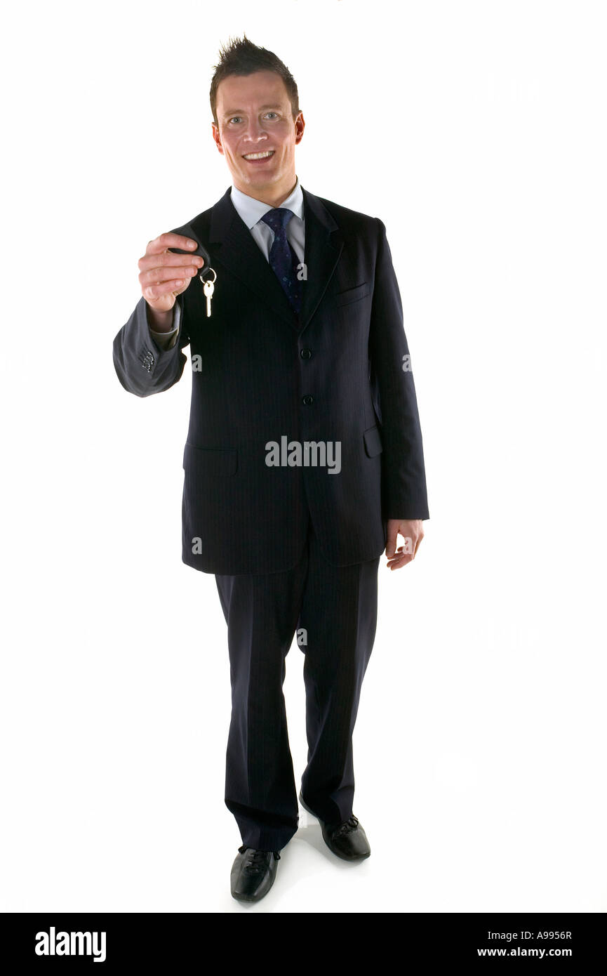 Businessman holding out a set of keys Stock Photo