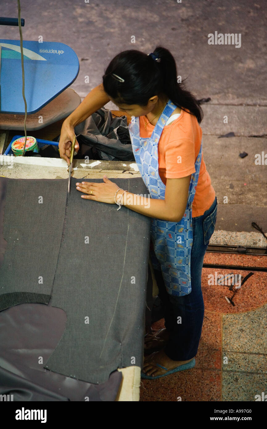 Young lady in a Bangkok sweatshop producing tailored suits for men Bangkok Thailand - Stock Image