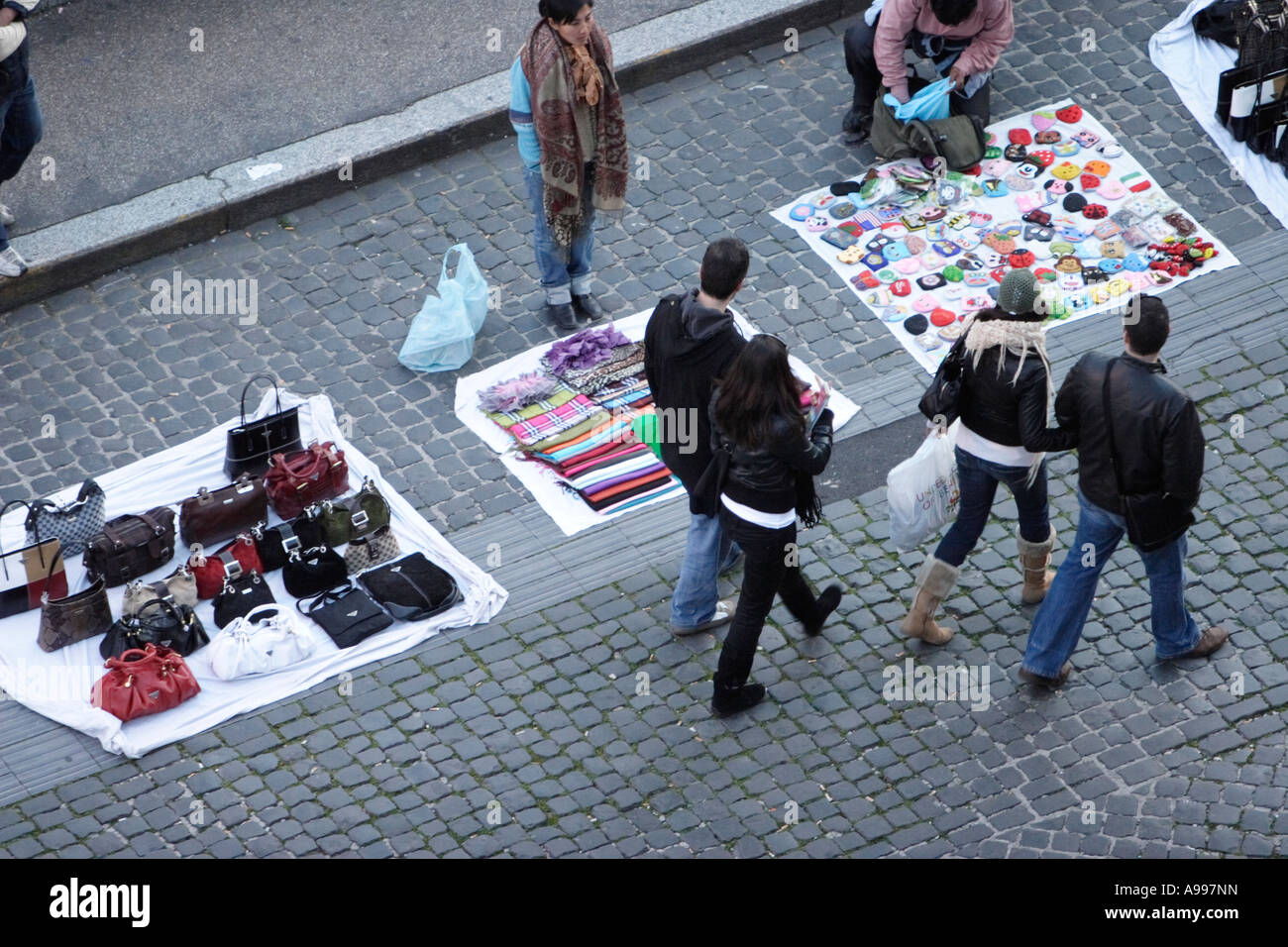 Tourists pass street trader with counterfeit designer goods in Rome, Italy Stock Photo