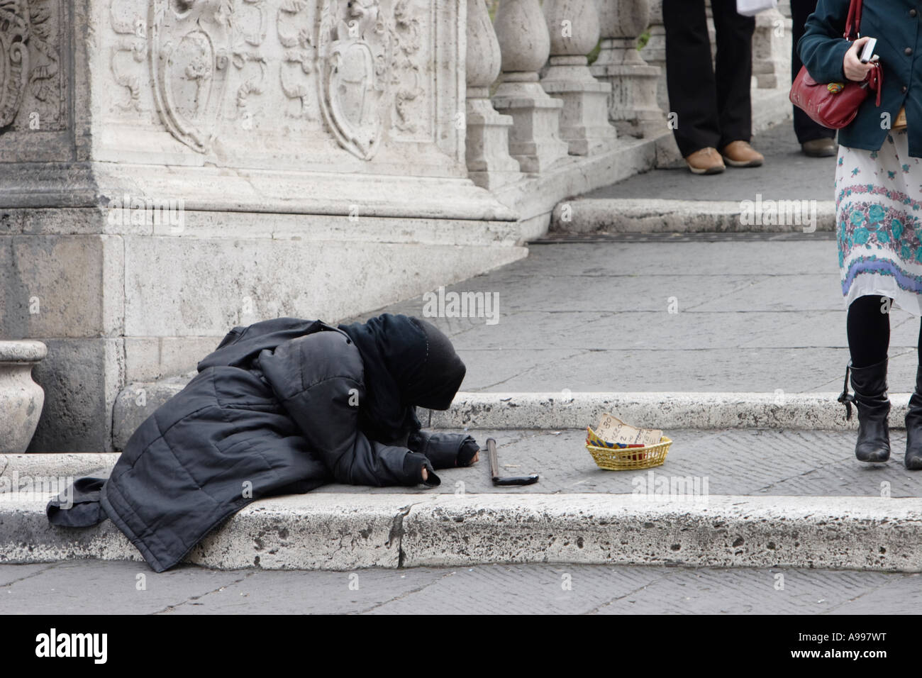 Beggar on the steps to the Palazzo dei Conservatori on Capitol hill in Rome, Italy - Stock Image
