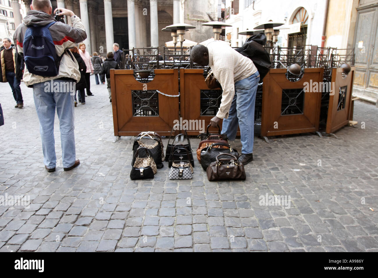 A street trader deals with designer handbags in Rome, Italy Stock Photo