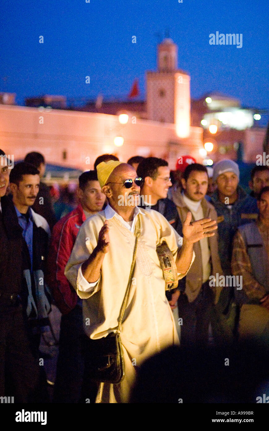 Crowd gathered around a popular storyteller and musician performing on the central square of Djemaa El Fna in Marrakesh - Stock Image