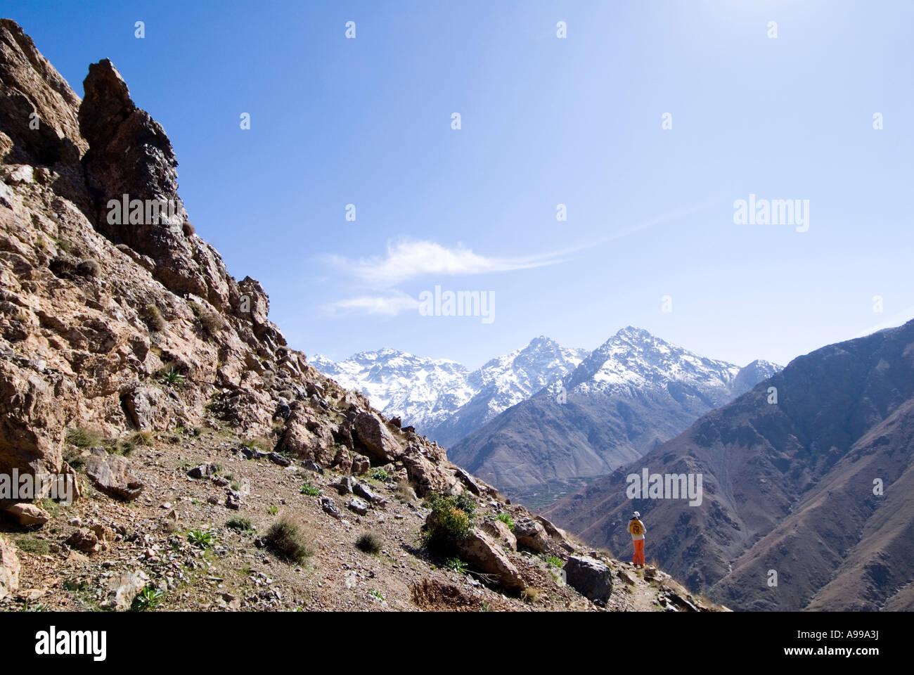 Trekker overlooking the vast Mizane Valley towards the snowy Toubkal mountain range of the High Atlas Mountains - Stock Image