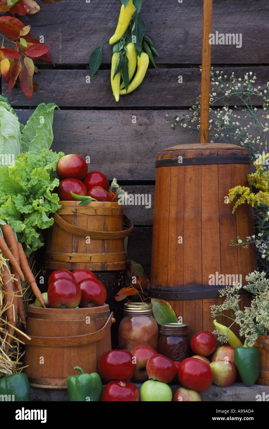 Harvested produce, antique churn and kitchen containers by old barn wall at an outdoor display of community farmer's market - Stock Image