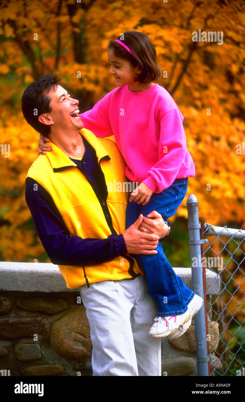 Hispanic father holding his young daughter and laughing Stock Photo