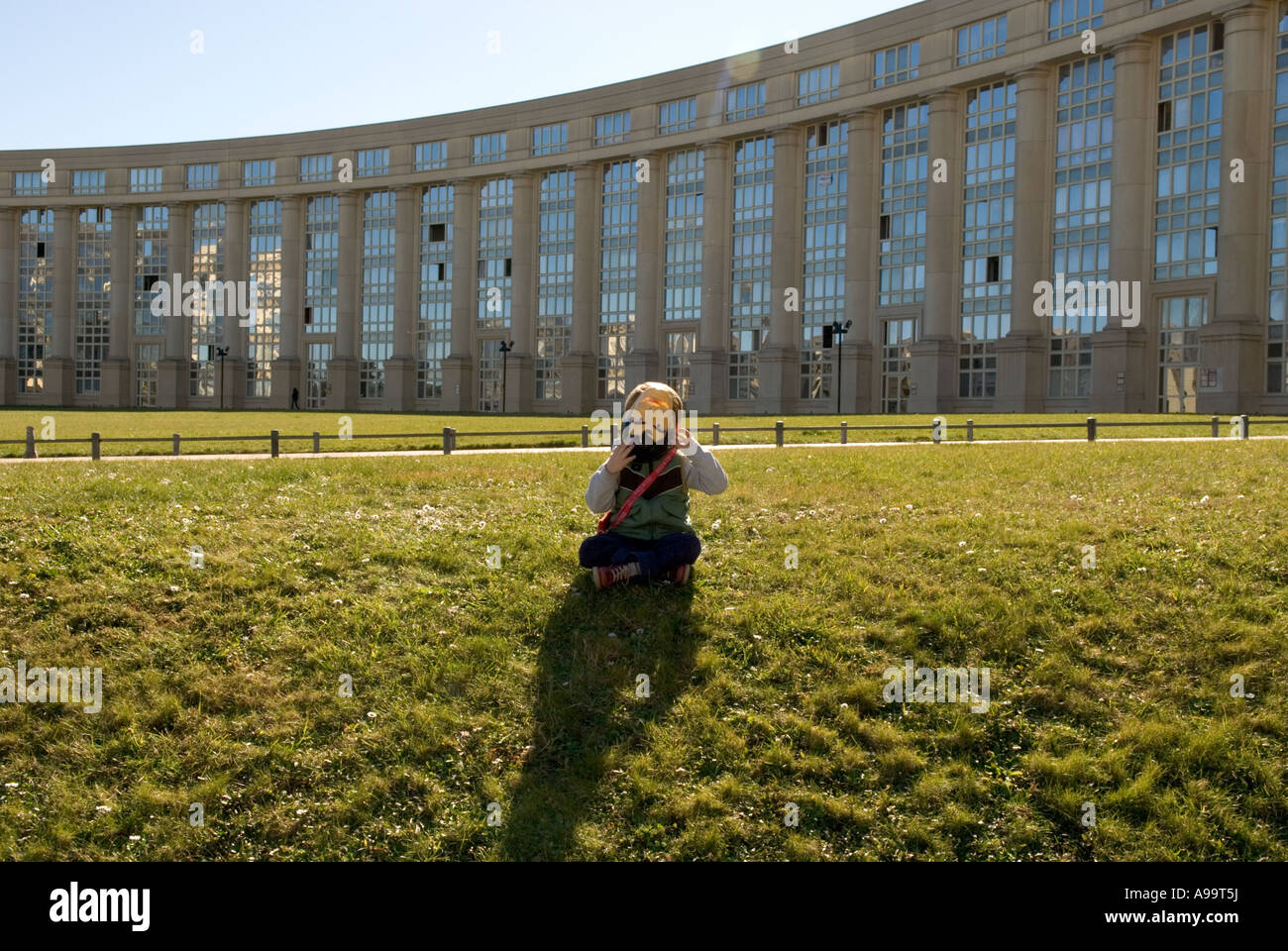 A close up of a child with superman mask sitting on grass in front of modern buildings in montpellier, france - Stock Image