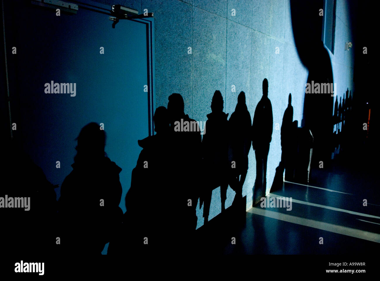 439 a line of full length shadows of people on a wall - Stock Image