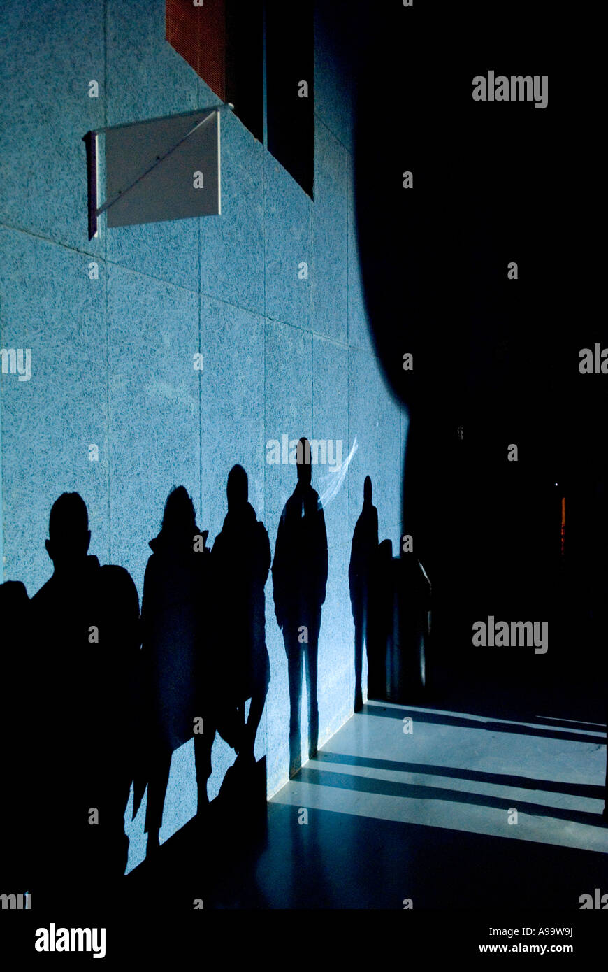 440 a line of full length shadows of people on a wall - Stock Image