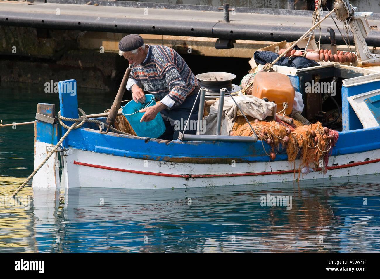 Sicilian fisherman on his boat at the docks Cefalu Sicily Italy - Stock Image