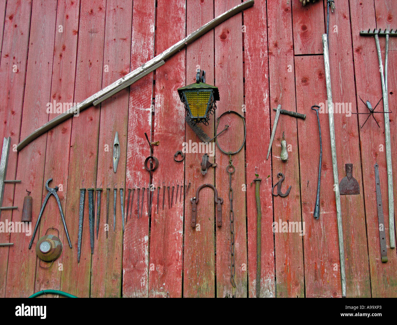 old iron tools and nails on wall of a red blockhouse log house - Stock Image
