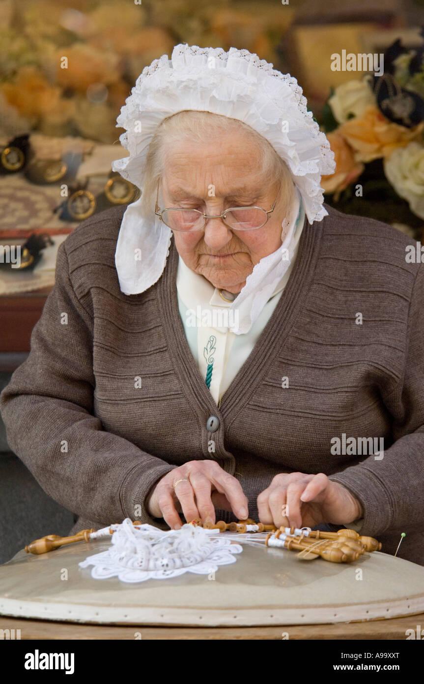 An old lady demonstrating the art of bobbin lace-making in Bruges (Brugge) Belgium. - Stock Image