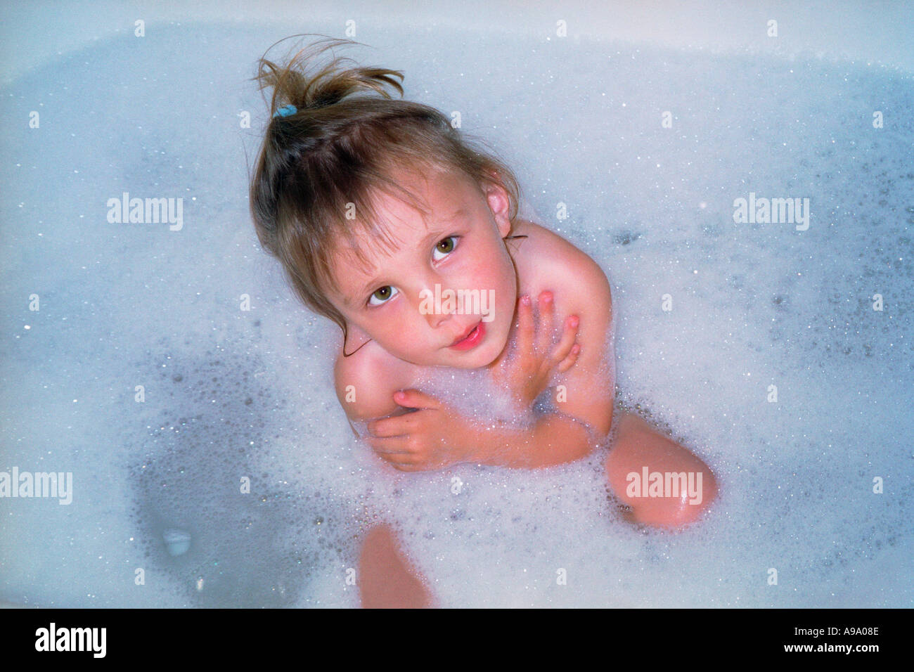 Warm water bath and bubbles surrounding beautiful little four year ...