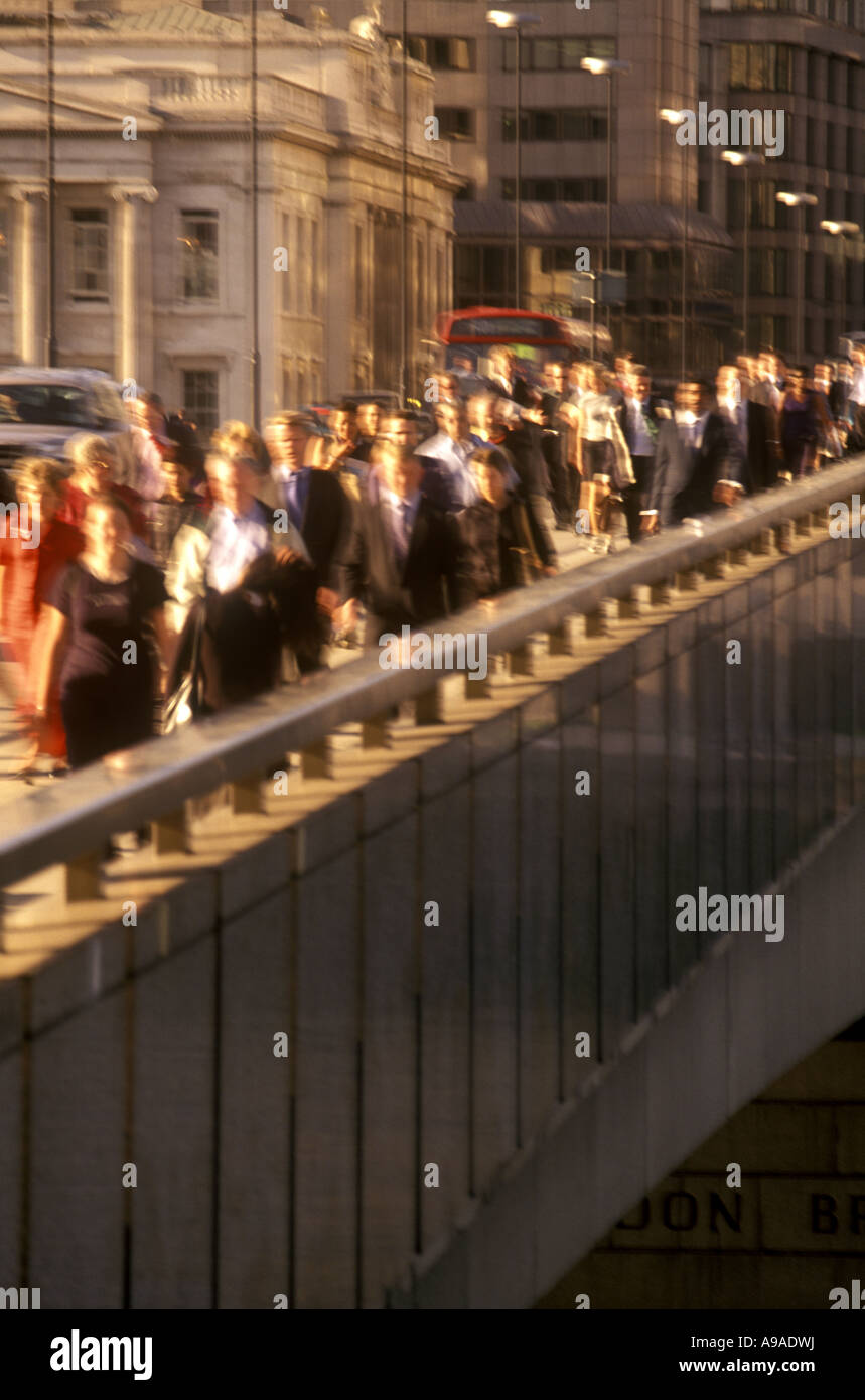 CROWDS OF OFFICE WORKERS CROSSING LONDON BRIDGE DURING RUSH HOUR LONDON ENGLAND UK - Stock Image