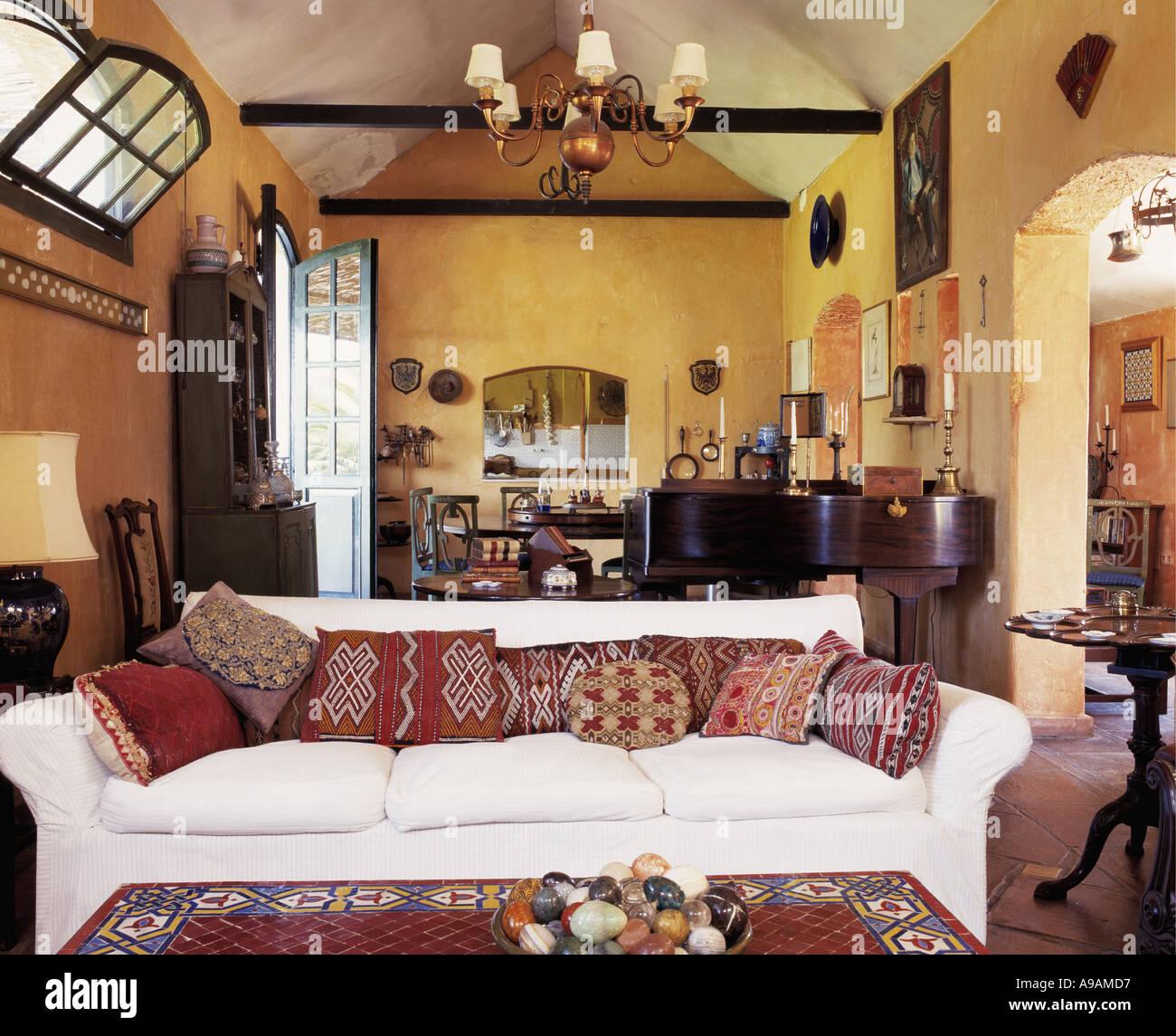 Kelim Cushions On White Sofa In Yellow Living Room In Spanish Villa
