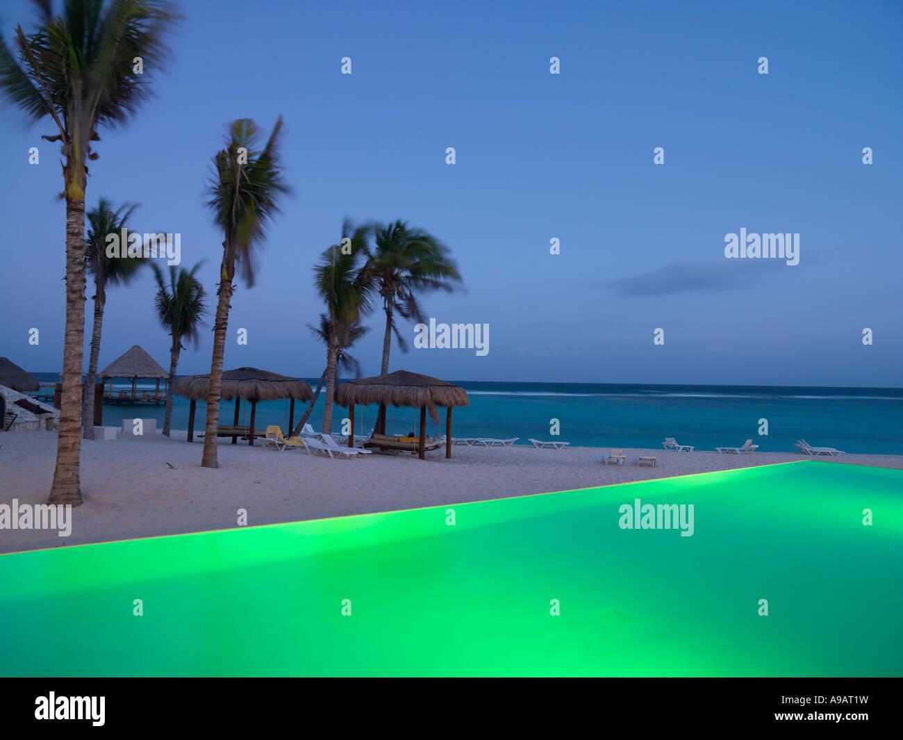Mexico Quintana Roo Yucatan Peninsula Akumal Mayan Riviera infinity pool illuminated by the edge of a beach with - Stock Image