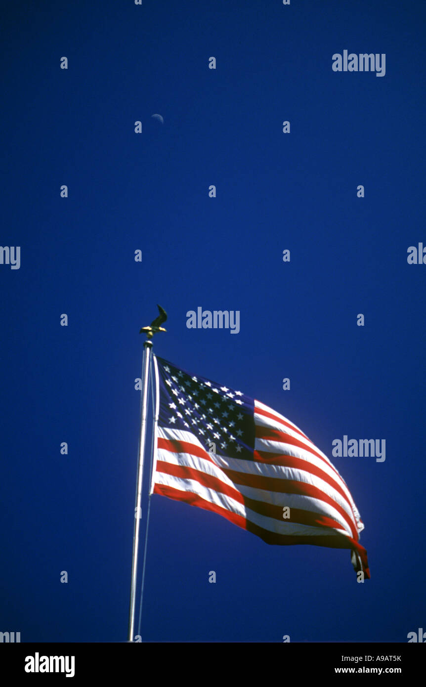 UNITED STATES  OF AMERICA FLAG FLYING ON FLAGPOLE WITH BLUE SKY - Stock Image