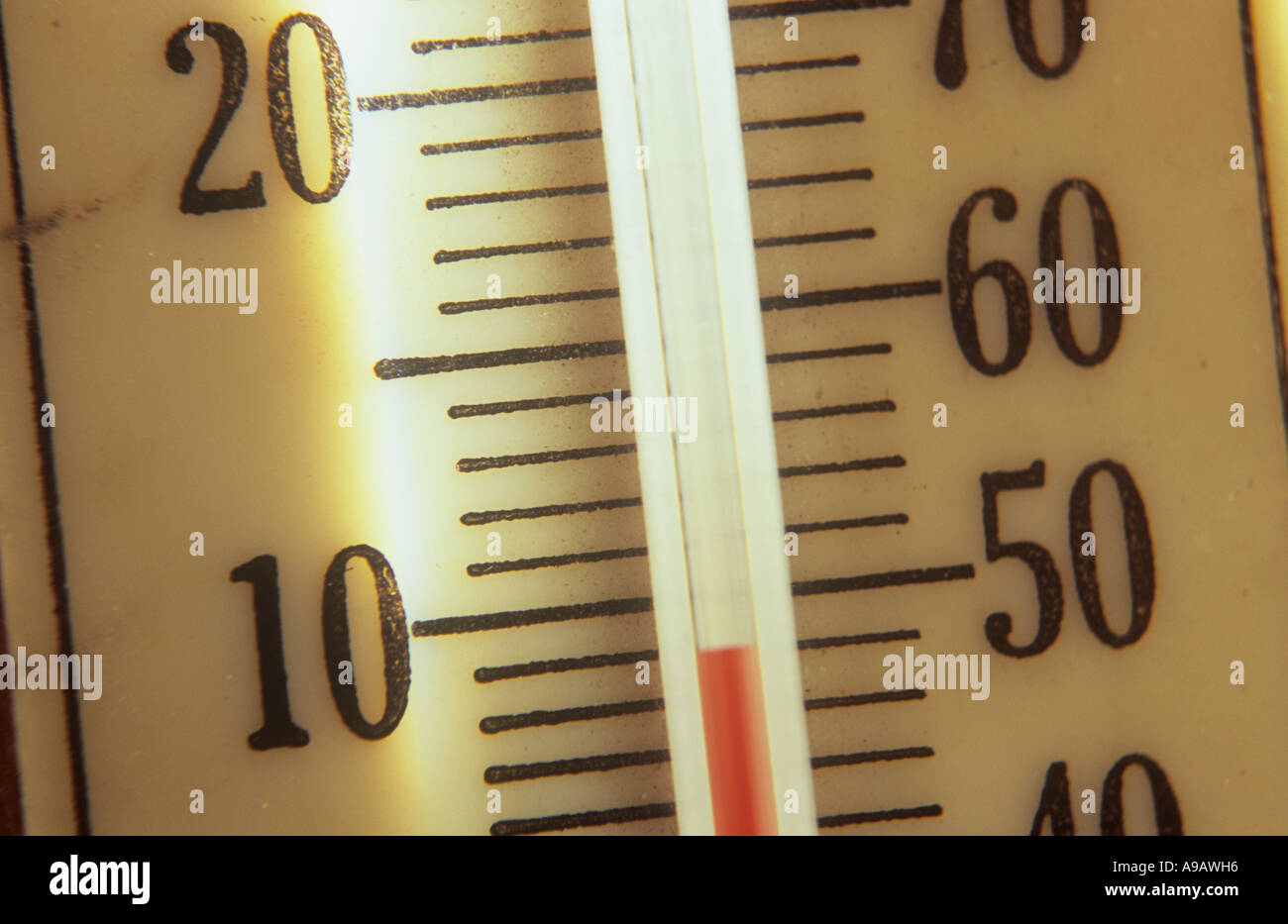 Close up detail of a backlit thermometer registering 9 degrees Celsius or 48 degrees Fahrenheit - Stock Image
