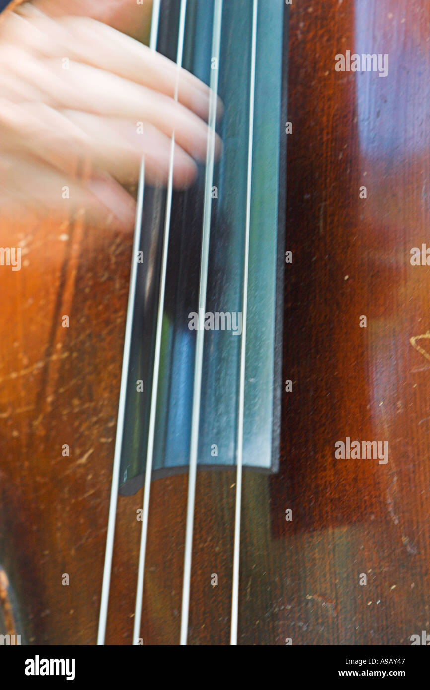 Male hand plucking strings on an upright bass Stock Photo