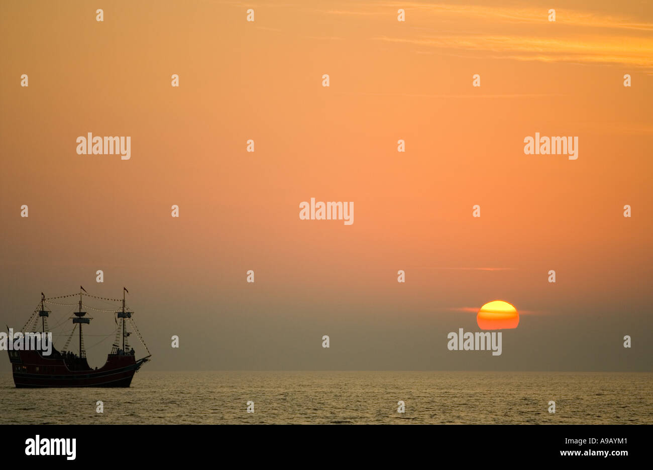 Replica of a pirate ship sailing at sunset - Stock Image