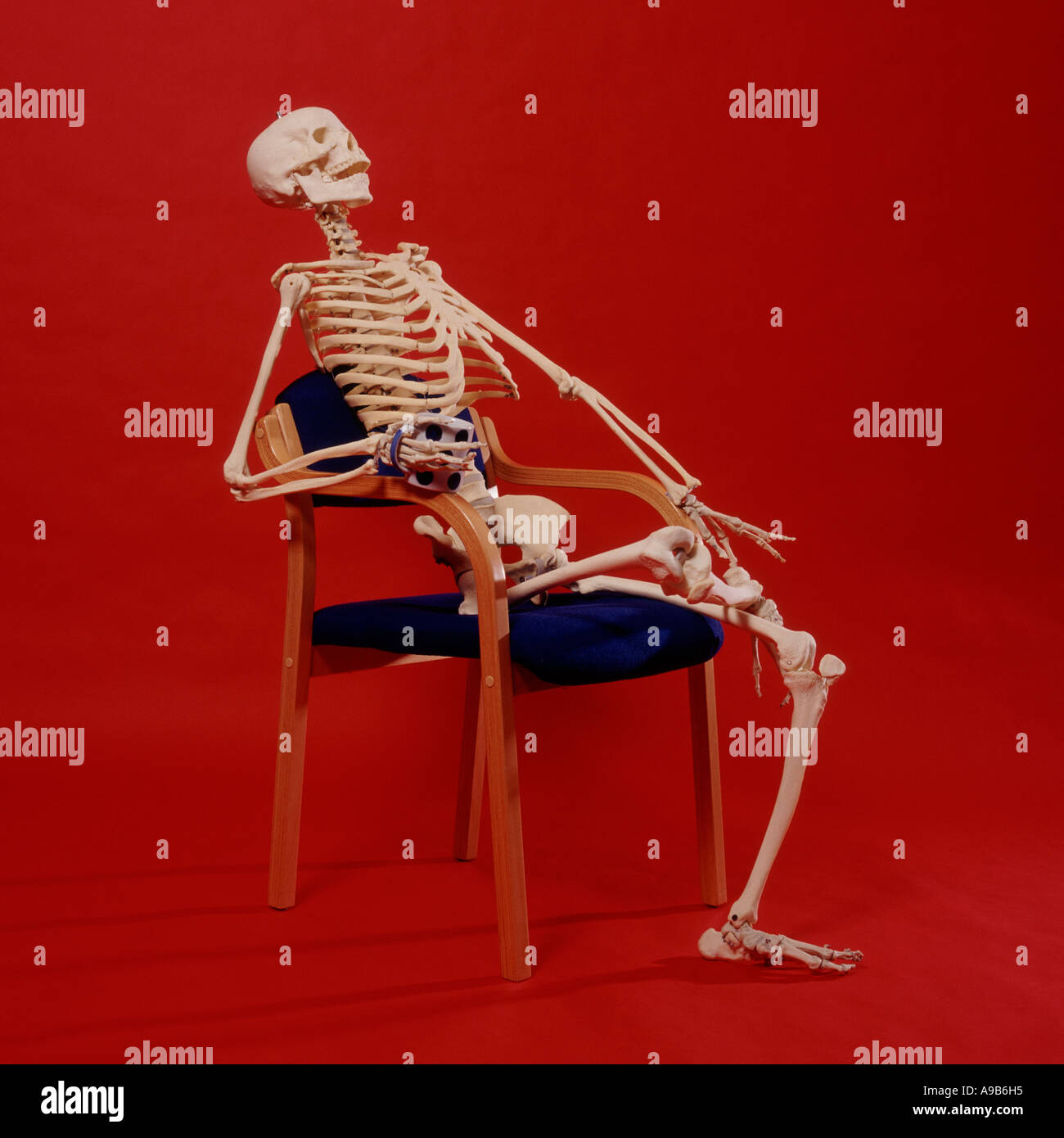 skeleton relaxing in a chair with a mug of tea or coffee in hand