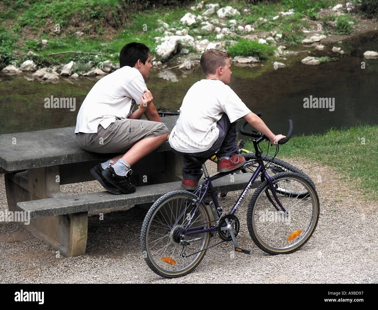 france two young teenage boys one with bicycle one sitting on bench looking into distance - Stock Image