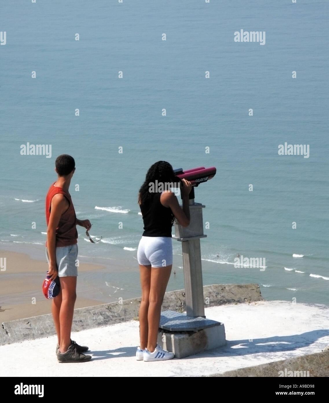 france teenage boy and girl looking through telscope across the english channel site des caps cap de blanc nez neear calais - Stock Image