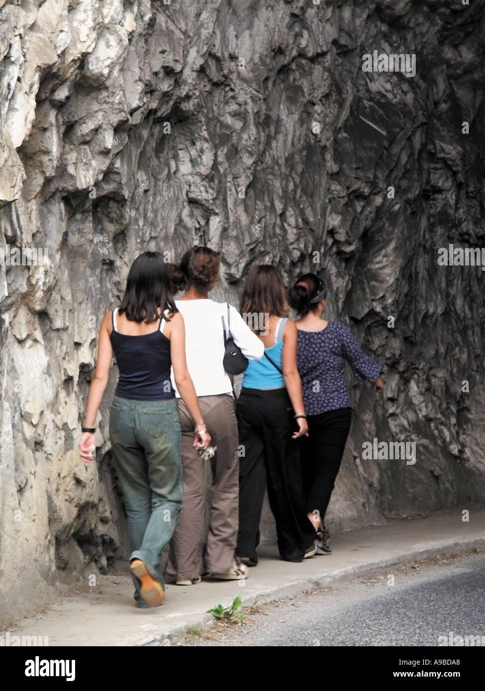 france four teenage girls walking along pavement through tunnel - Stock Image