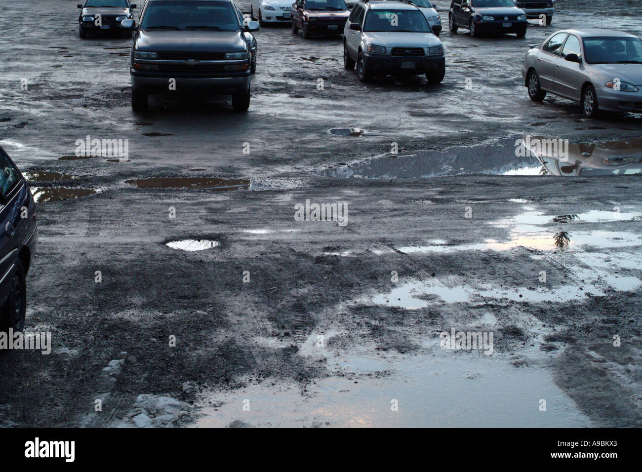 Muddy parking lot with puddles - Stock Image
