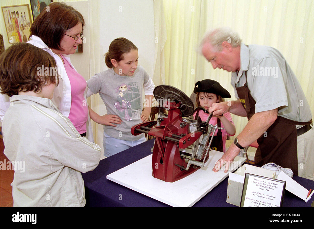 Wigtown Book Festival child using a Adana Eight Five hand press part of a demonstration in Wigtown Scotlands National - Stock Image