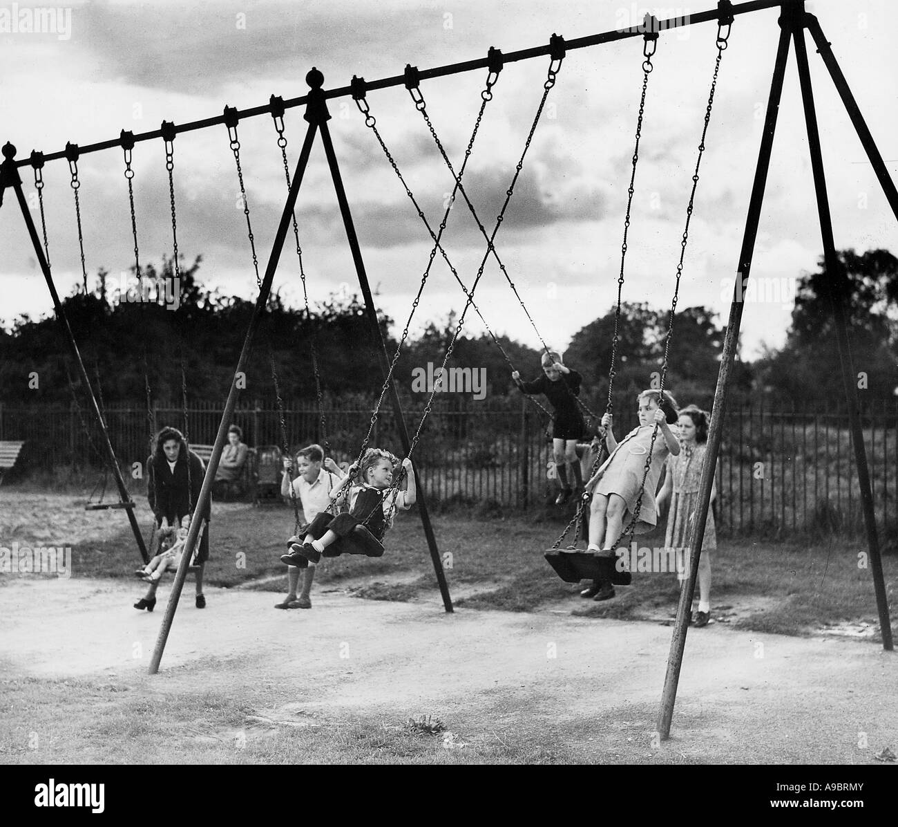 CHILDREN ON SWINGS in 1943- these are evacuees from London - Stock Image