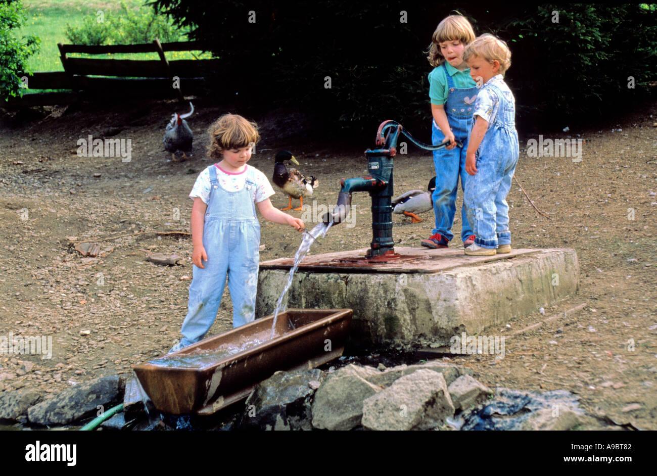 kids enjoying fountain at farmstead - Stock Image