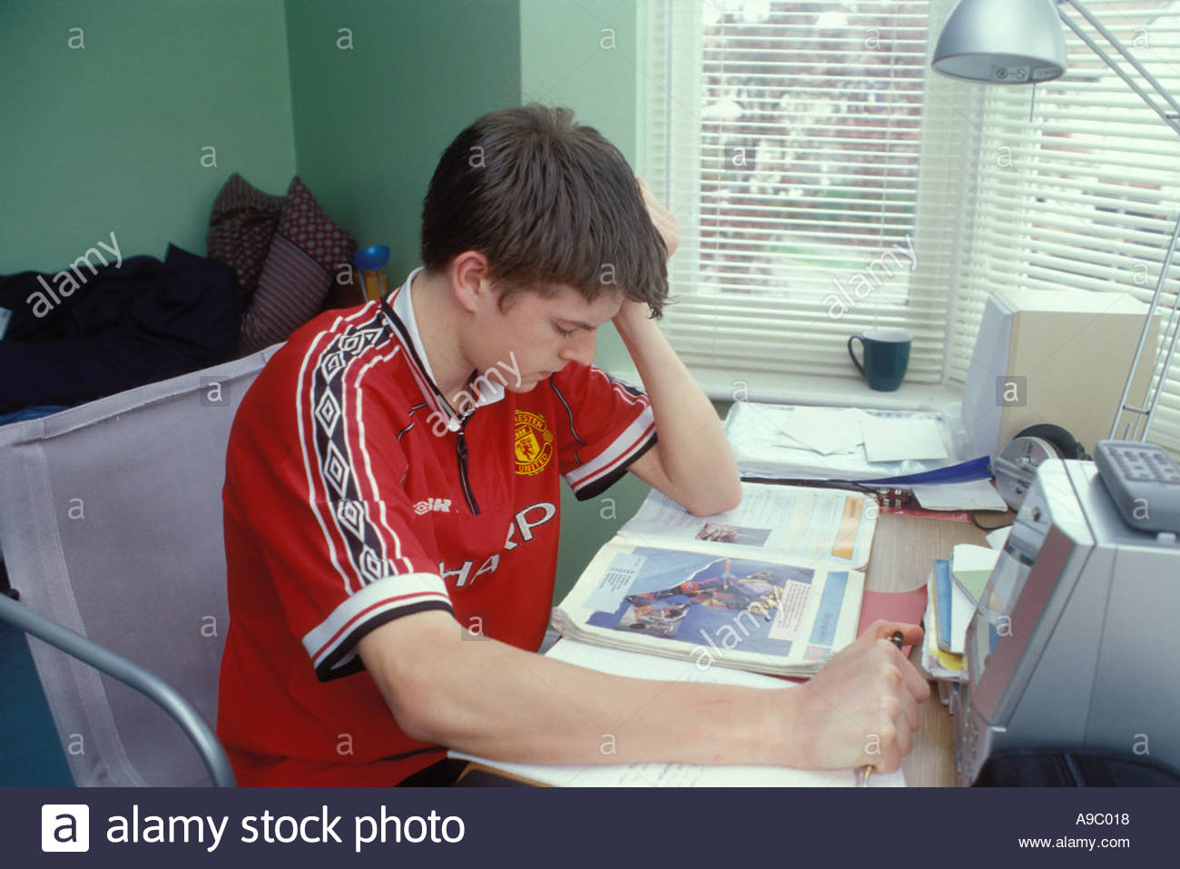 15 Year Old Schoolboy Doing His Homework In His Bedroom At Home Uk Stock Photo Alamy