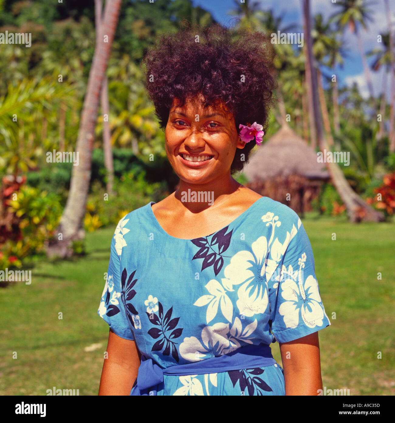 Hibiscus flower hair stock photos hibiscus flower hair stock fijian girl with a pink hibiscus flower over her left ear in traditional style flowered dress izmirmasajfo