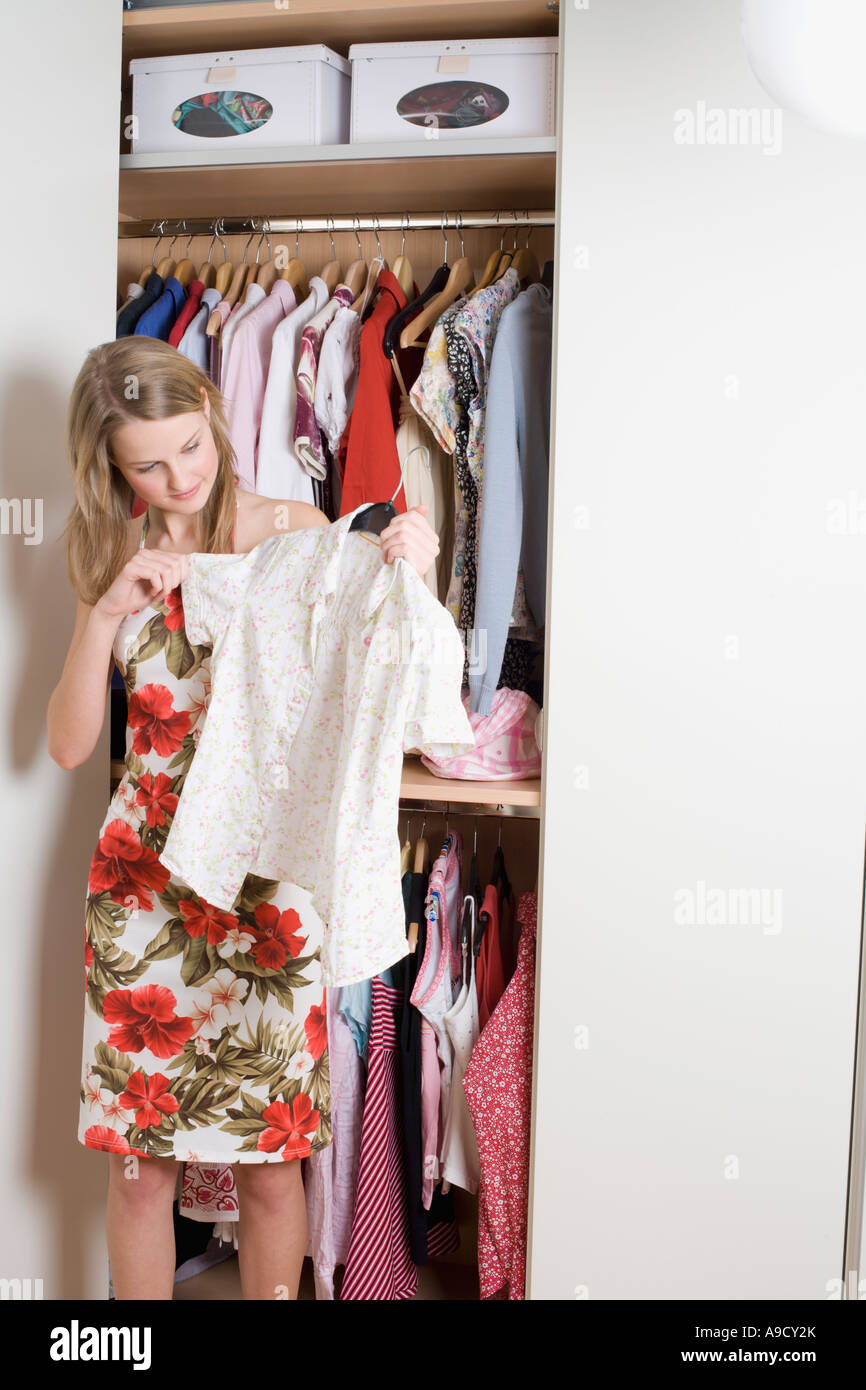 Teenage Girl Checking Blouse In Front Of Open Wardrobe