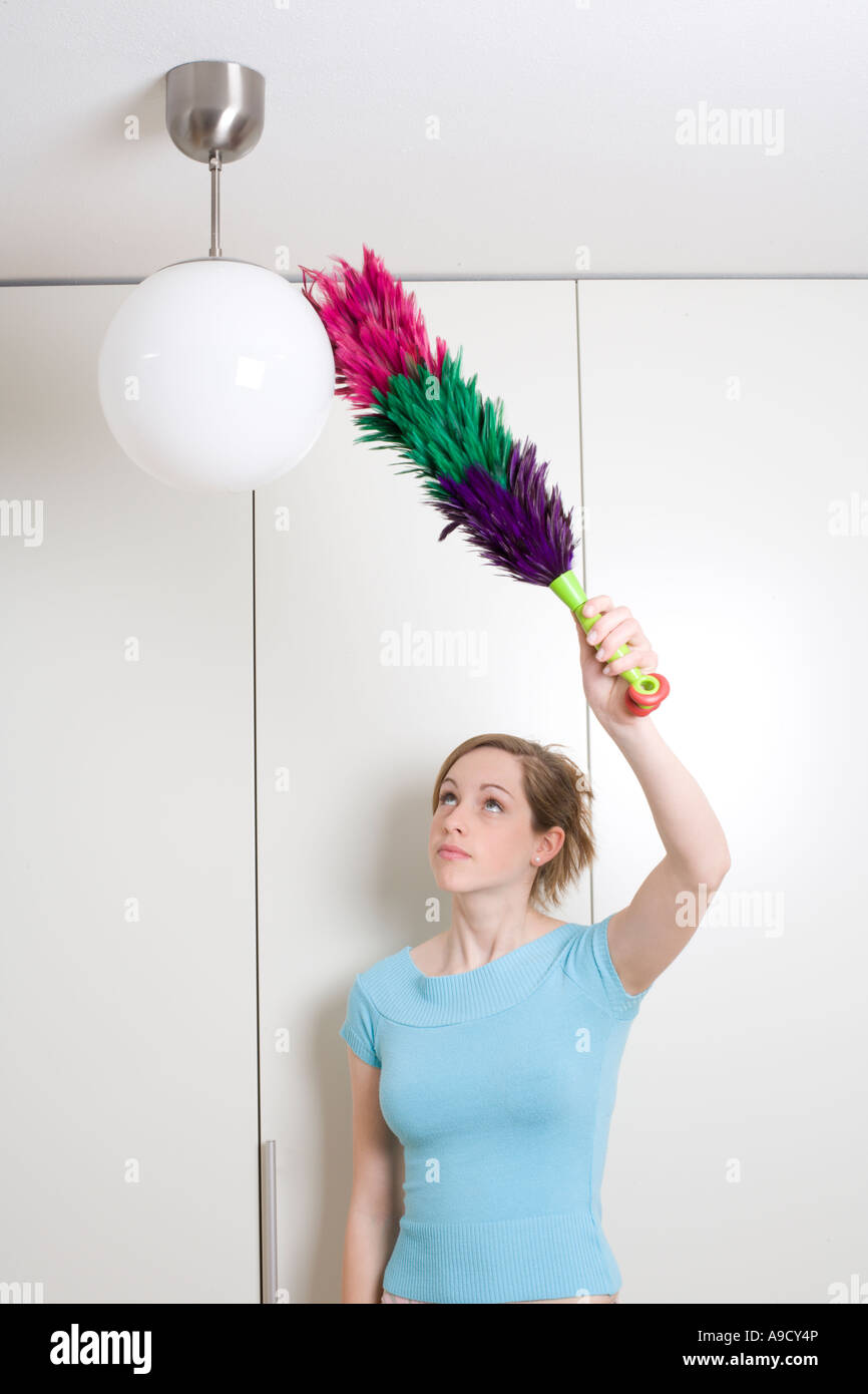 young woman dusting lamp with feather duster - Stock Image