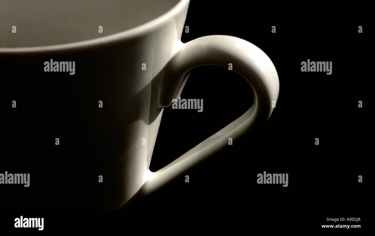 Detail of a cup rim and handle against a black background - Stock Image