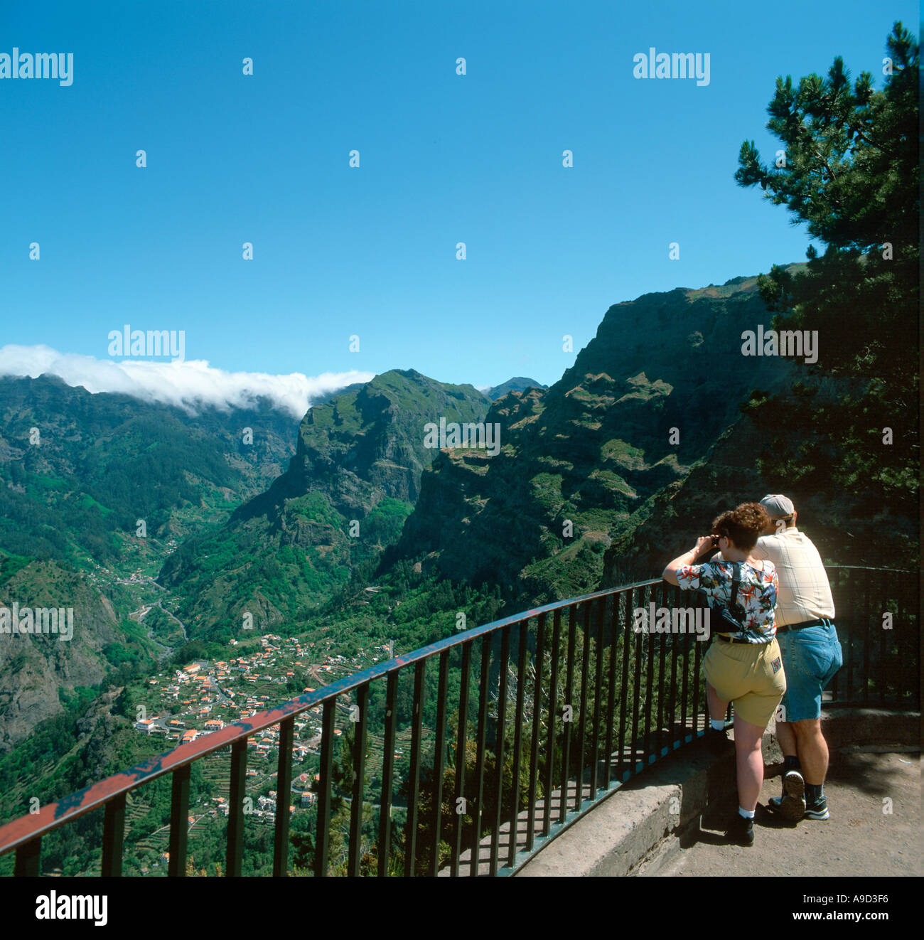 Couple at a viewpoint overlooking the mountain village of Curral das Freiras, Madeira, Portugal - Stock Image