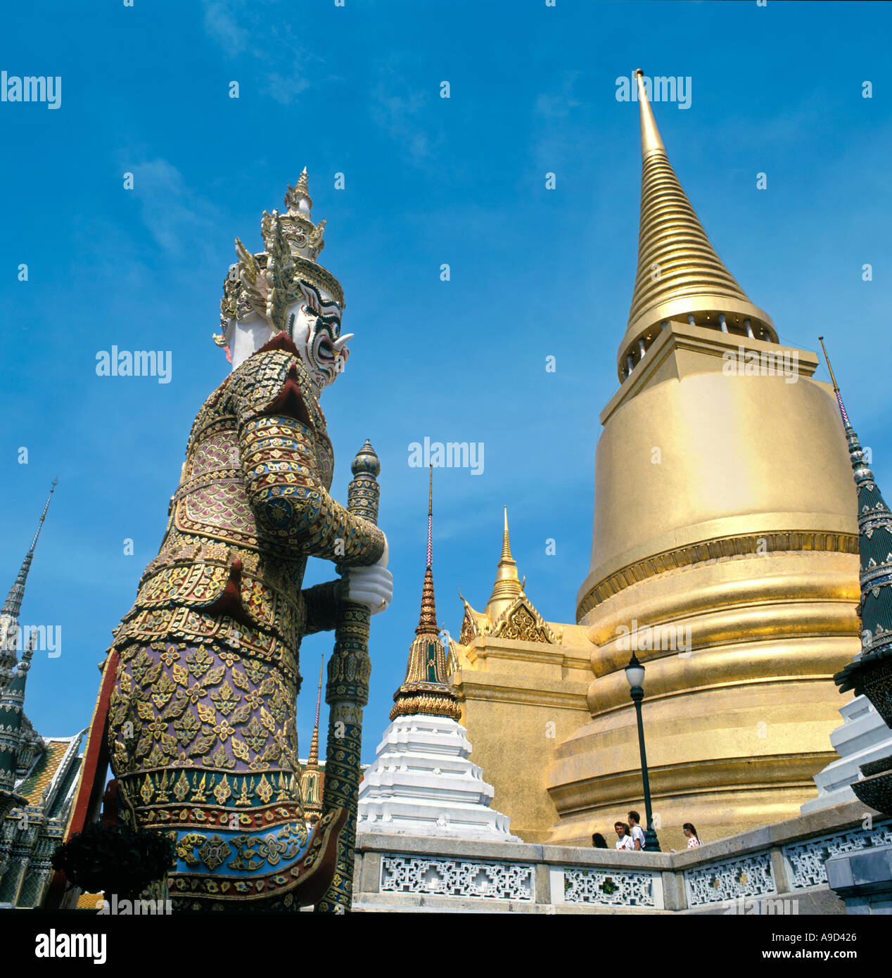 Giant statue on the upper terrace with the Phra Sri Ratana Chedi behind, Grand Palace, Bangkok, Thailand - Stock Image