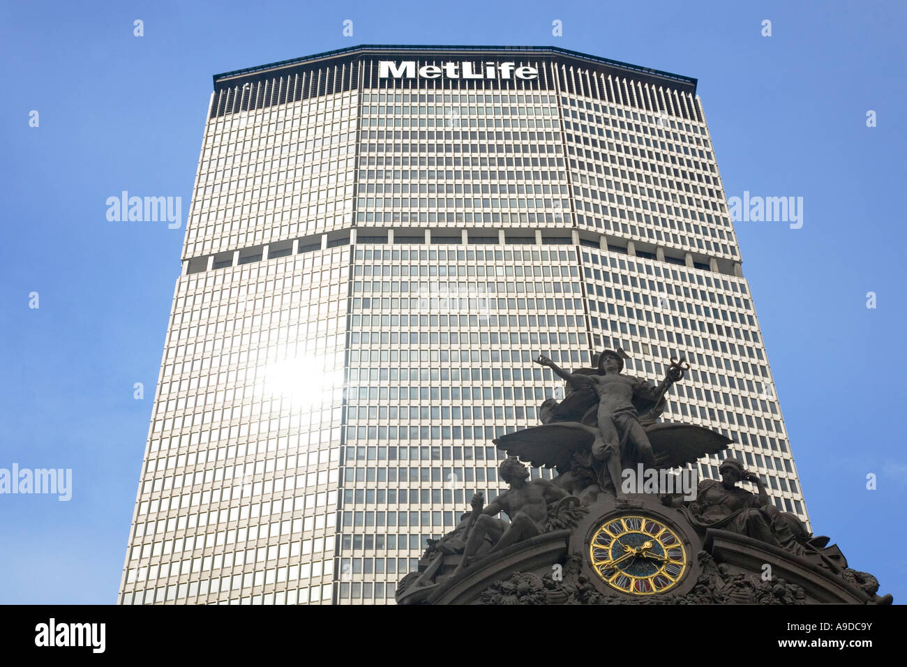Grand Central Station Clock and Met Life building in sun sunshine with blue sky with skyscapers in midtown Manhattan - Stock Image