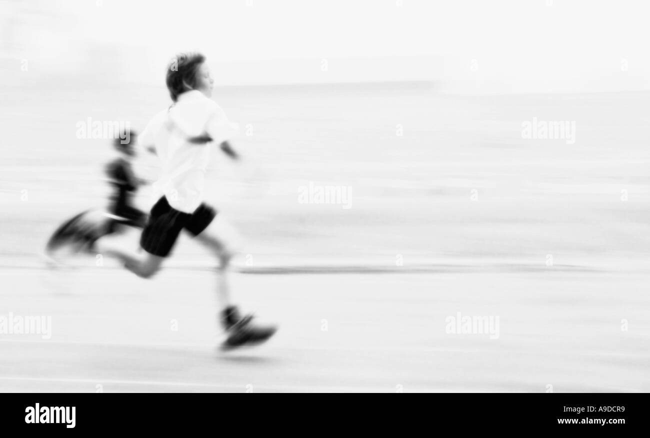 Student competes in 100m sprint race. High key black and white. - Stock Image