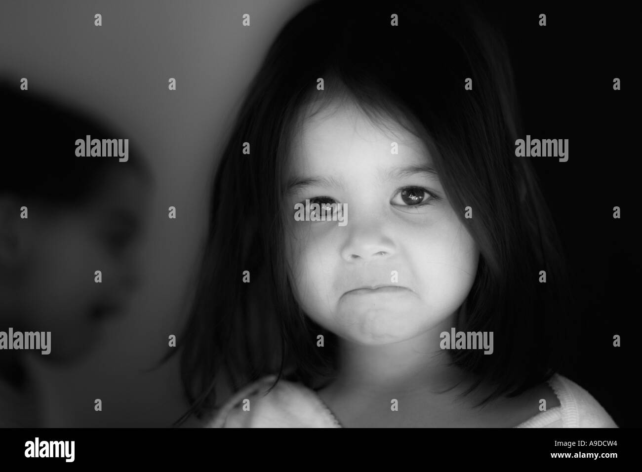 Girl with brother in the background shadows - Stock Image