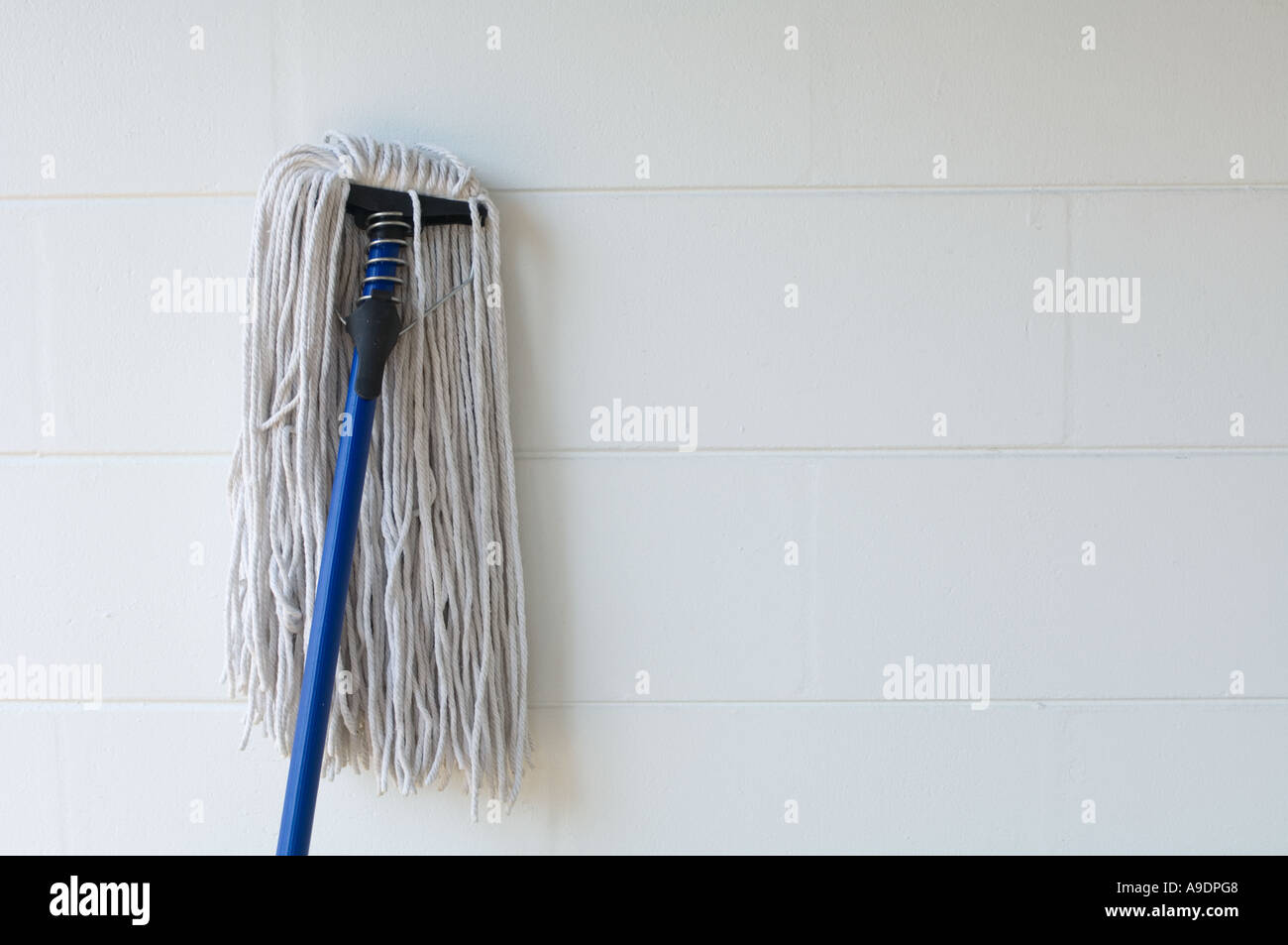 old fashioned rope mop leaning against wall - Stock Image