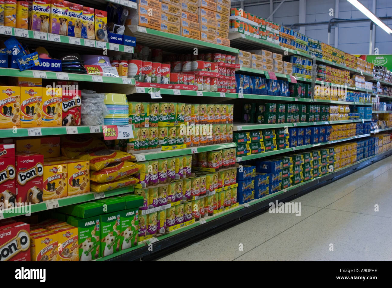 Tins of dog food and pet accessories on a supermarket shelf - Stock Image