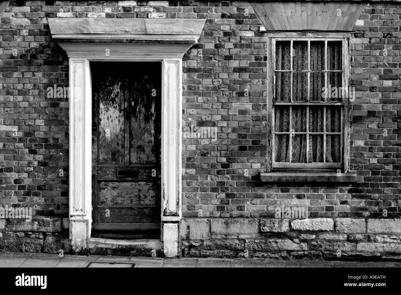 A run down Georgian terraced house desperately in need of some tender loving care. Black and White version (Landscape - Stock Image