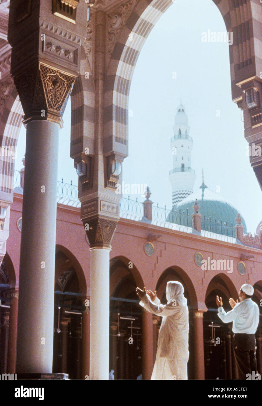 Saudi Arabia, Mecca.  A Muslim raises his hands in prayer in the Mosque. Mecca & Medina are two of the holiest - Stock Image