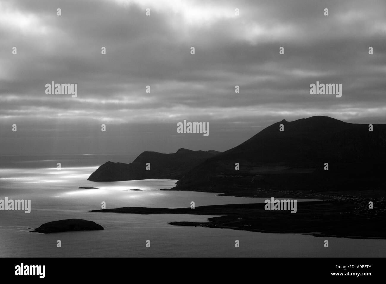 Silhouetted coastline of Achill Island, Ireland, lit by beams of light breaking through the clouds. - Stock Image