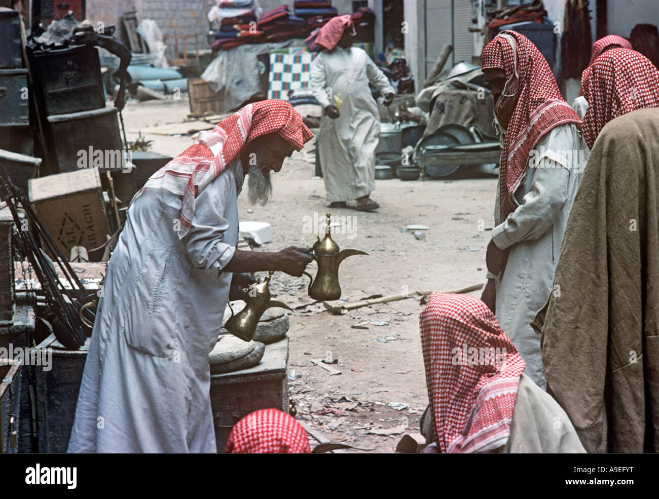 Saudi Arabia, Riyadh. A market seller offers a coffee pot for sale in the market place. - Stock Image